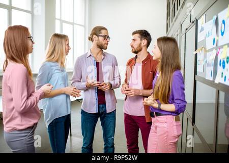 Junges Team von Mitarbeitern gekleidet beiläufig zusammen gesprochen in der Nähe der Glaswand mit einige Statistiken und Aufkleber im Büro - Stockfoto