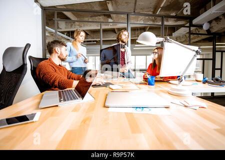 Gruppe von jungen Mitarbeiter gekleidet beiläufig zusammen auf dem Computer in das moderne Büro innen