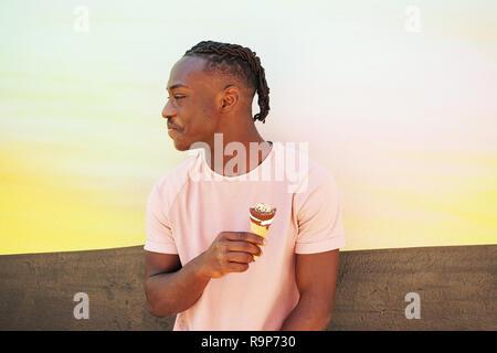 Junge hübsche schwarze Mann trägt ein rosa t-shirt, hält und isst ein Eis im Sommer auf einer bemalten Wand wie ein Sonnenaufgang oder sonnigen Tag - Stockfoto