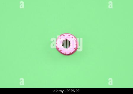 Einzelne kleine Plastik Donut liegt auf einem pastel farbigen Hintergrund. Flach minimalen Komposition. Ansicht von oben - Stockfoto