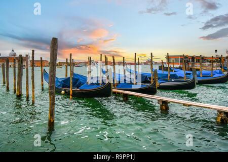Gondeln am Pier entlang des Canal Grande, wie die Sonne in Venedig, Italien