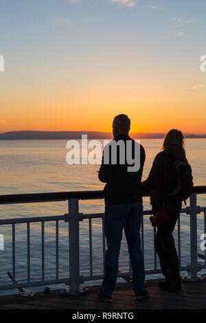 Bournemouth, Dorset, Großbritannien. 27 Dez, 2018. Schönen Sonnenuntergang über Bournemouth Strand am Ende einer schönen sonnigen Tag, wie die Besucher der Seebrücke und Strand die Sonne zu beobachten. Paar. Credit: Carolyn Jenkins/Alamy leben Nachrichten