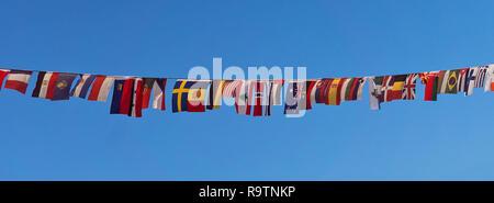 Reihe der kleinen Flaggen verschiedener Länder auf einem Seil vor blauem Himmel - Stockfoto