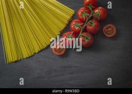 Spaghetti und frische Tomaten auf einer schwarzen Platte. Köstliche italienische Küche. Hintergrund für essen oder kochen. - Stockfoto