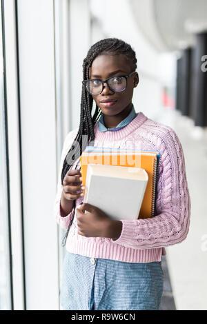Junge afrikanische Student Frau Notebooks halten vor dem Vortrag in der Nähe von Fenstern in der Universität - Stockfoto