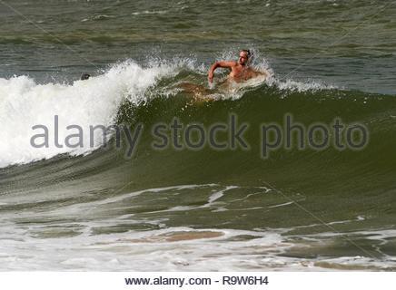 Eine männliche Surfer dreht seinen Kopf Meer zu vermeiden - Spray, als er Paddel sein Surfbrett über den Kamm der Welle; während eine Surf Session in Yamba, Australien. - Stockfoto