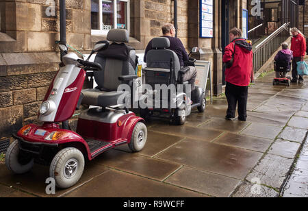 Drei Mobilität scooters außerhalb von befestigten Straßen im Zentrum von Lancaster, Großbritannien - Stockfoto