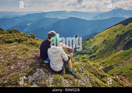 Junges Paar wandern unter selfie mit Smart Phone. Glückliche junge Mann und Frau unter Selbstportrait mit Bergkulisse im Hintergrund. - Stockfoto