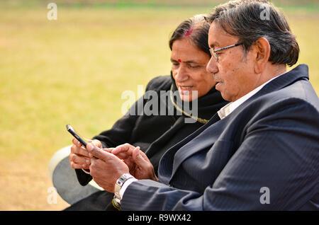 Senior Paar sitzt im Park mit Blick auf das Telefon und lächelnd in Delhi, Indien - Stockfoto