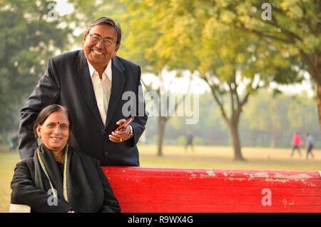 Gerne suchen pensionierte ältere indische Mann und Frau paar Lächeln und sich an der Suche in einem Park im Freien - Stockfoto