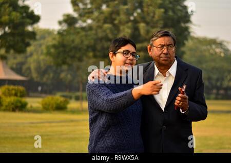 Junge indische Frau mit kurzen Haaren mit seinem Vater in einer lebhaften Diskussion in Richtung etwas in einem Park in Delhi, Indien, - Stockfoto