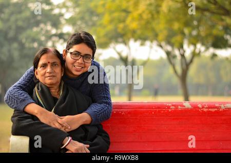 Junge indische Frau lachend mit ihrer Mutter, die auf einer roten Bank in einem Park in Delhi, Indien sitzt. - Stockfoto