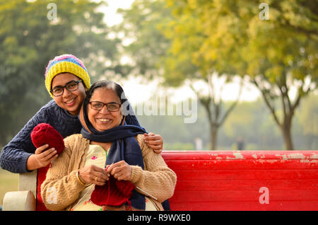Gerne suchen junge indische Frau mit ihrer Mutter Stricken Pullover, die auf einer roten Bank in einem Park in Delhi, Indien sitzt. - Stockfoto