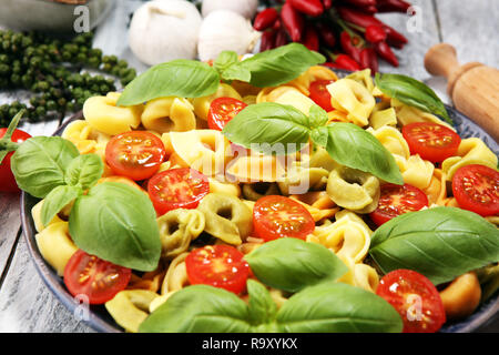 Pasta. tricolor Tortellini Pasta Salat mit Tomaten und Zwiebeln auf Holz Tisch Hintergrund - Stockfoto