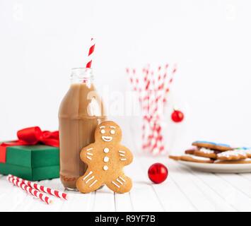 Lebkuchen in der Nähe der Flasche mit Schokolade Milch und abisolierten Stroh auf weißem Hintergrund in der Weihnachtszeit - Stockfoto