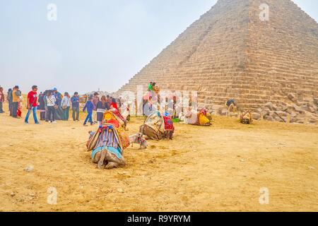 Gizeh, Ägypten - Dezember 20, 2017: Die Gruppe der Touristen neben Menkaure Pyramide in Giza Necropolis bereitet sich auf Kamel reiten, Kamele sitzen auf dem Sand, - Stockfoto