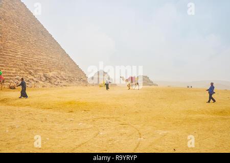 Gizeh, Ägypten - Dezember 20, 2017: Ägyptische bedouin Treibern in der traditionellen Kleidung bieten Tourist Transport Service auf Kamelen in der Pyramide, Deze - Stockfoto