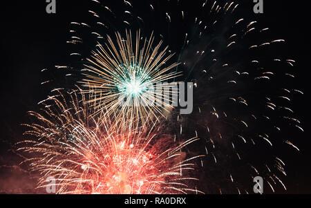 Mehrfarbig glänzende Feuerwerk im dunklen Nachthimmel explodieren.