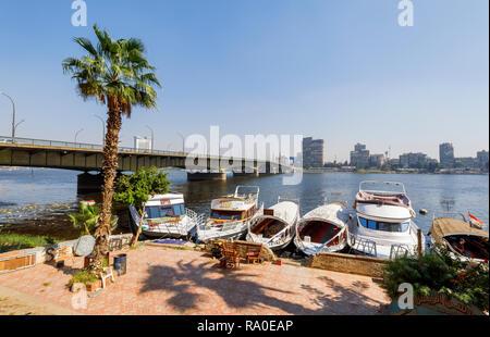 Boote am Ufer von der Universität Kairo Brücke über den Nil in Giza, Kairo, Ägypten, auf der Suche nach Osten Bank an einem sonnigen Tag - Stockfoto
