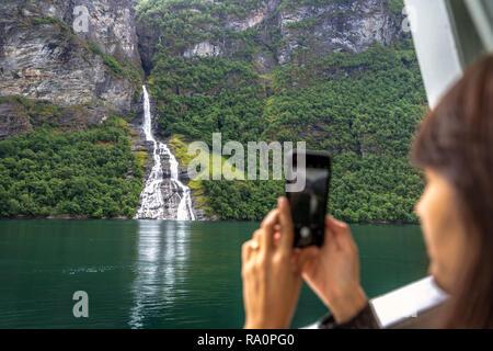 Fjorde, Norwegen - 5. Juni 2018 - Junge Frau, die ein mobiles Bild von einem Wasserfall in den Fjorden Norwegens - Stockfoto