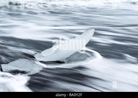 Eisbrocken von einem Gletscher auf Diamond Beach, ein schwarzer Sandstrand in Island gebrochen - Stockfoto