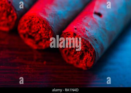 Nahaufnahme von Zigarren im Neonlicht - Stockfoto