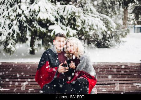 Verliebtes Paar sitzt auf der Bank und lächelnd in Schnee Wald. - Stockfoto