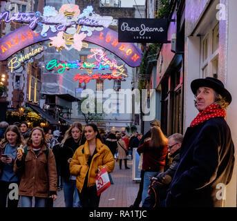 Mann mit dem roten Schal & Mütze lehnt sich gegen die Wand, wie Leute von Einkaufen gehen, Carnaby Street, London, Weihnachten Neon Licht Installation. Dez. 2018 - Stockfoto