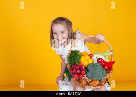 Kleine schöne Mädchen, dass ein Korb mit frischem Obst und Gemüse gesunde Ernährung - Stockfoto