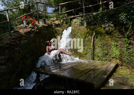 Eine schwarze Frau badet im Freien in einem Fass unter einem Wasserfall. Nationalpark Krka, Šibenik-Knin, Dalmatien, Kroatien, Europa - Stockfoto