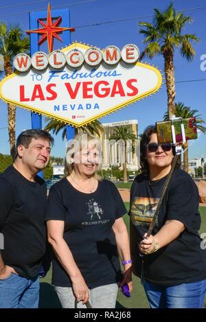 """Mann mit zwei Frauen posieren für Fotos mit einem selfie Stick vor der berühmten, Vintage, """"Welcome to Fabulous Las Vegas, Nevada""""-Schild an den Eingang - Stockfoto"""