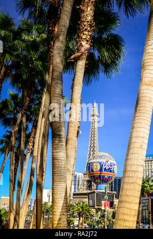Ein Blick durch die Stämme der Palmen auf dem Las Vegas Strip gegenüber dem Paris Las Vegas Hotel und Kasino, unterschiedliche mit faux Eiffelturm, NV - Stockfoto