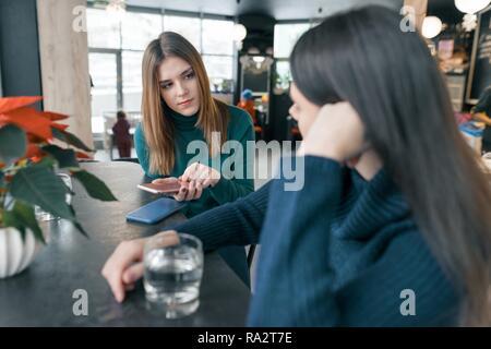 Sprechen junge Frauen, Mädchen im Winter cafe lächelnd und sprechen, Sitzen, trinken sauberes Wasser in Glas und über Handy, rot Weihnachtsstern Weihnachten