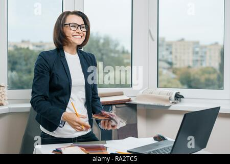 Weibliche Dekorateur Innenarchitekt am Arbeitsplatz mit Stoffmuster, Laptop. Lächelnd weibliche in Jacke, Gläser auf die Seite, während in der Nähe von ständigen - Stockfoto