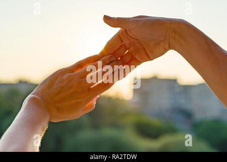 Hände zusammen mit Geste der Finger, Symbol der Freundschaft und Beziehung. Hintergrund Abend Sonnenuntergang, Stadt Silhouette. - Stockfoto