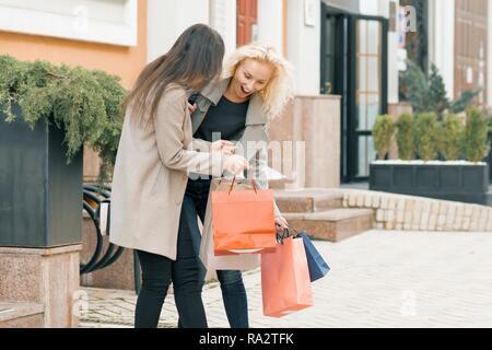 Zwei junge lächelnde Frauen auf einer Straße der Stadt mit Tüten, sonnigen Herbsttag, goldene Stunde. - Stockfoto
