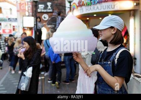 Ein japanisches Mädchen mit bunten Baumwolle Zuckerwatte auf Takeshita Straße im Stadtteil Harajuku in Tokio, Japan. - Stockfoto