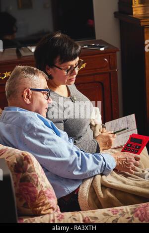 Paar Senioren Haushalt Rechnungswesen mit Taschenrechner und Planung zu Hause. - Stockfoto