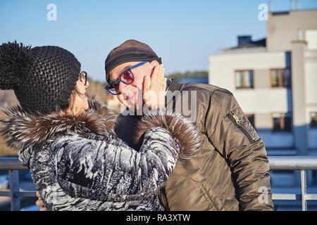 Glückliche freudige Senioren Paar warm gekleidet stehen auf dem Balkon gegen den Himmel. - Stockfoto