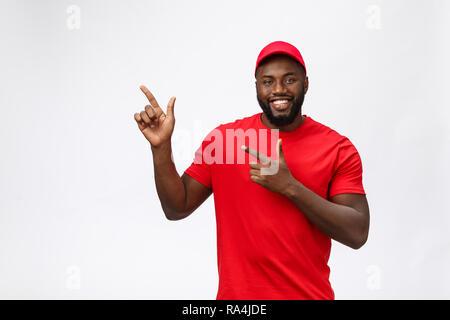 Lieferung Konzept - Portrait von Happy African American Delivery Man zeigende Hand etwas zu präsentieren. Auf Grau studio Hintergrund isoliert. Platz kopieren - Stockfoto