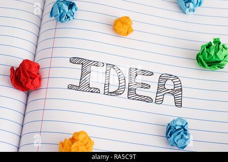 Idee. Idee Wort auf Notebook Blatt mit einigen bunten zerknittertes Papier Kugeln auf. Close Up. - Stockfoto