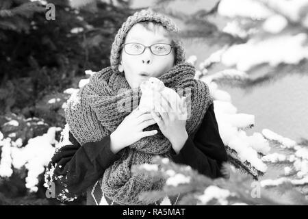 Kleine überrascht junge oder netten nerd Zicklein in der Brille, Mütze, Pullunder und Modischer Strickschal hält Schwein Kässeli im Winter im Freien auf der grünen Tanne mit Schnee auf den natürlichen Hintergrund - Stockfoto
