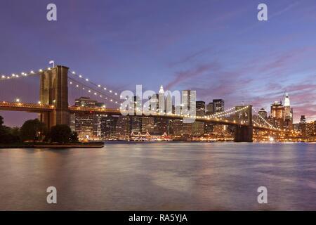Brooklyn Bridge vor der Skyline von Manhattan am Abend, Manhattan, New York City, New York, United States - Stockfoto