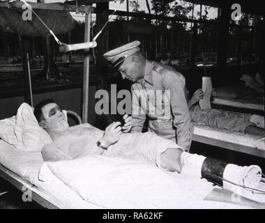 Ein verwundeter Soldat liegt auf einem Krankenhausbett und hält die Auszeichnung, während Brig. Gen. Denit beugt sich über ihn. - Stockfoto