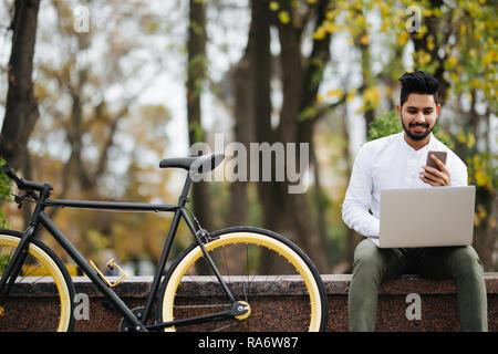 Glückliche junge indische Mann mit Handy während der Arbeit am Laptop sitzen im Freien in der Nähe Fahrradverleih - Stockfoto