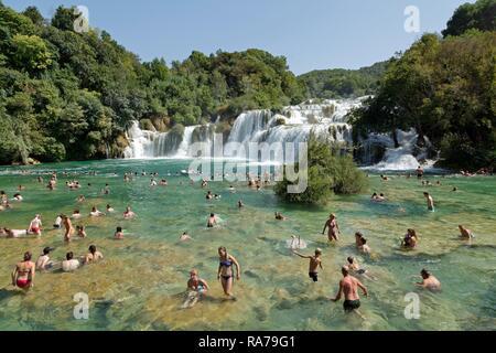 Menschen schwimmen vor einem Wasserfall, Krka Nationalpark, Dalmatien, Kroatien - Stockfoto