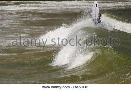Eine junge männliche Surfer - Tülle - Ausführen einer vertikalen Antenne Trick auf seinem Surfbrett, wie der Shore-break Wave schließt heraus; bei Yamba, NSW, Australien. - Stockfoto