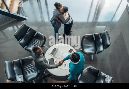 African Business Kollegen Gruß und Dank nach einer erfolgreichen Tagung. Zwei Frau umarmen und zwei Männer sind die Hände schütteln - Stockfoto