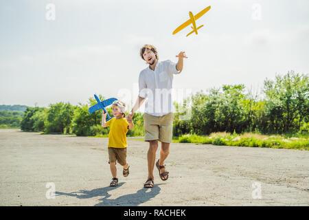 Gerne Vater und Sohn spielen mit Spielzeug Flugzeug gegen alte Landebahn Hintergrund. Mit Kindern unterwegs Konzept - Stockfoto