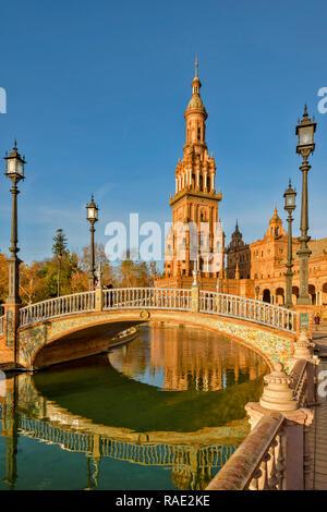 PALACIO ESPANOL IM PARQUE DE MARIA LUISA SEVILLA SPANIEN DEN TURM UND verzierten Fliesen- Brücke am frühen Morgen REFLEXIONEN IN DEN KANAL - Stockfoto